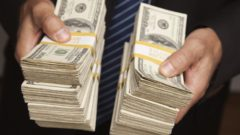 businessman-handing-over-stacks-of-hundred-dollar-bills