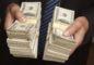 businessman-handing-over-stacks-of-hundred-dollar-bills