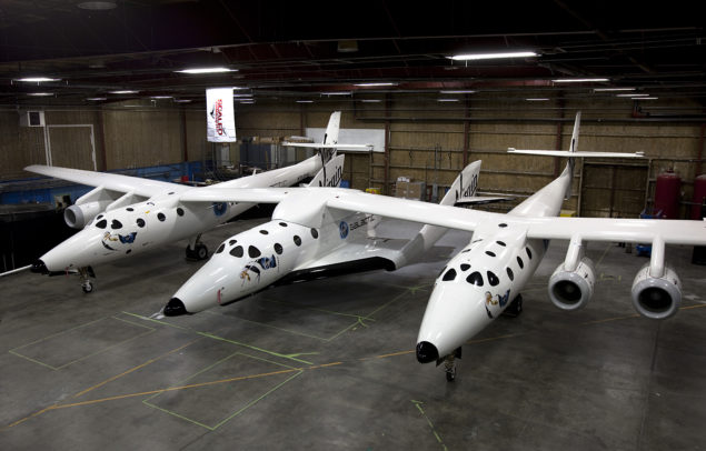 "SpaceShipTwo resting under the Mothership WhiteKnight2 inside a hangar in Mojave,Ca. SpaceShipTwo will have its worldwide debut Monday evening at the Mojave airport for dignitaries and future ""astronauts""."