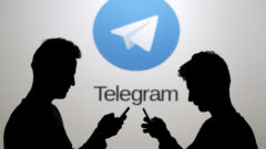 file-photo-men-pose-with-smartphones-in-front-of-a-screen-showing-the-telegram-logo-in-this-picture-illustration