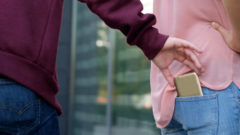 thief-stealing-the-wallet-from-the-bag-of-distracted-woman