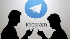file-photo-men-pose-with-smartphones-in-front-of-a-screen-showing-the-telegram-logo-in-this-picture-illustration-2